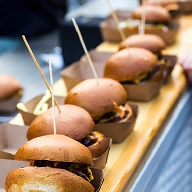 Unhealthy street food burgers with meat and cheese at an outdoor festival venue